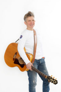Suli Puschban im Stehen mit umgehängter Gitarre
